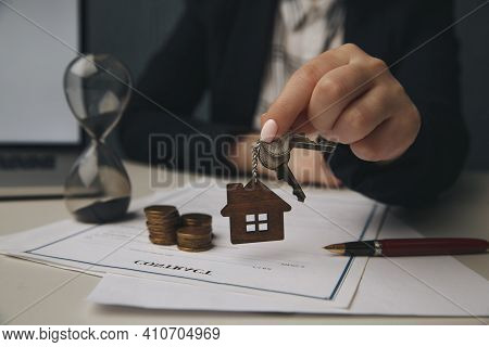 Close Up Wooden Toy House With Woman Signs A Purchase Contract Or Mortgage For A Home, Real Estate C