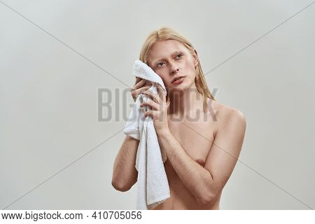 Shirtless Young Caucasian Man With Long Fair Hair Wiping His Face Using White Towel While Posing On