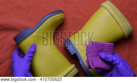 Hands In Purple Rubber Gloves Clean And Wipe Dirty Pair Of Kids Yellow Boots With Wet Rag. Top View
