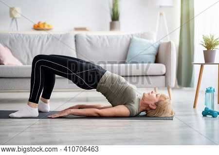 Stay At Home Fitness. Strong Mature Woman Doing Half Bridge Yoga Pose, Strengthening Her Abs Muscles