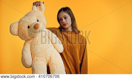 Displeased Teenager In Sweater Looking At Teddy Bear Isolated On Yellow