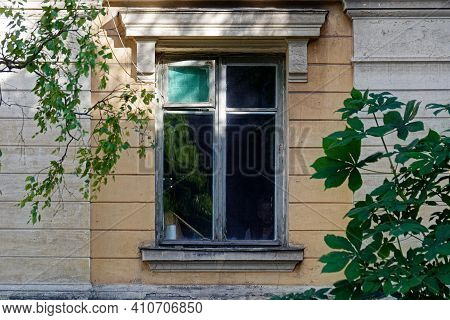 Rectangular Dirty Window With An Old Frame With A Cornice On A Yellow Wall With Cracked Plaster And