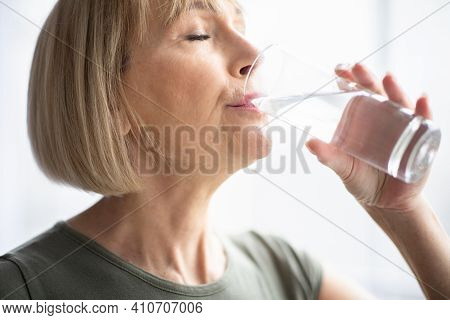 Portrait Of Sporty Mature Woman Drinking Water During Her Workout Indoors. Fit Mature Lady Staying H