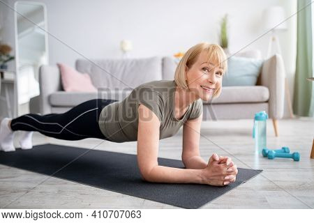 Home Training Concept. Smiling Senior Woman Doing Elbow Plank On Yoga Mat In Living Room. Positive M
