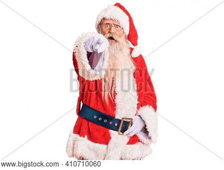 Old senior man with grey hair and long beard wearing traditional santa claus costume pointing displeased and frustrated to the camera, angry and furious with you