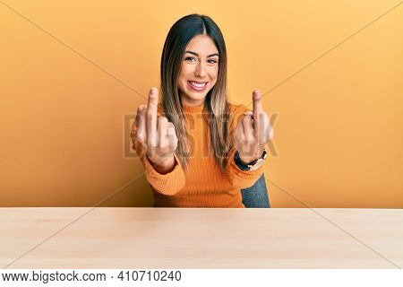 Young hispanic woman wearing casual clothes sitting on the table showing middle finger doing fuck you bad expression, provocation and rude attitude. screaming excited