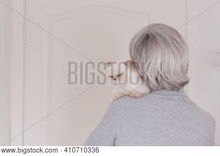 A Gray-haired Older Woman In A Gray Turtleneck Has A Cute Beige Purring Cat On Her Shoulder. The Vie