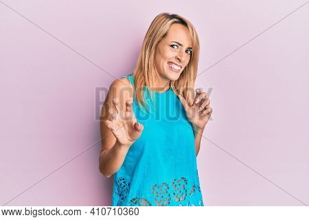 Beautiful blonde woman wearing casual clothes disgusted expression, displeased and fearful doing disgust face because aversion reaction. with hands raised