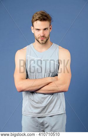 Proud To Be Strong. Man Sporty Outfit Looks Serious And Strict With Folded Arms, Violet Background.