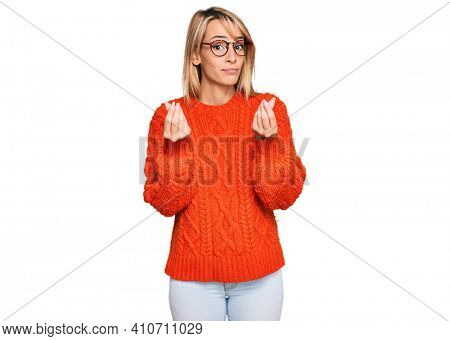 Beautiful blonde woman wearing casual clothes and glasses doing money gesture with hands, asking for salary payment, millionaire business