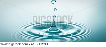 Water drop falling and drips on water mirror. Water drop splash and make perfect circles on water surface