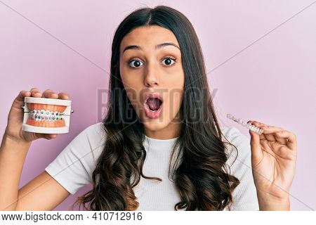 Young hispanic woman holding invisible aligner orthodontic and braces afraid and shocked with surprise and amazed expression, fear and excited face.