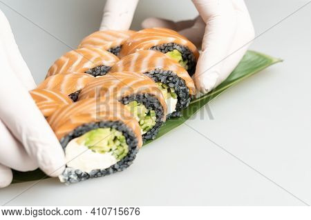 Closeup Of Chef Hands Preparing Japanese Food. Japanese Chef Making Sushi At Restaurant. Young Chef