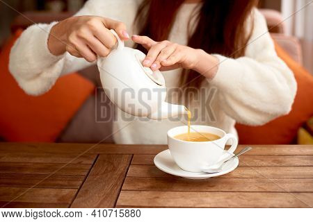 Girl Drinking Herbal Detox Tea In Cafe. White Cup Table In Cafe. Woman Drinking Tea On Wooden Table