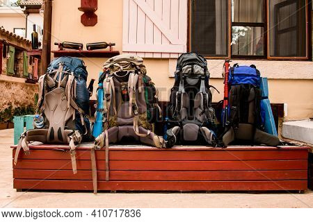 Several Big Bright Hiking Backpacks Lies On The Bench.