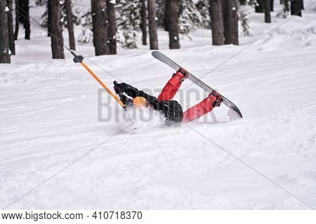 A Snowboarder Who Has Lost His Balance Does Not Let Go Of The Crossbar Of The Lift Bugel. He Rolls B