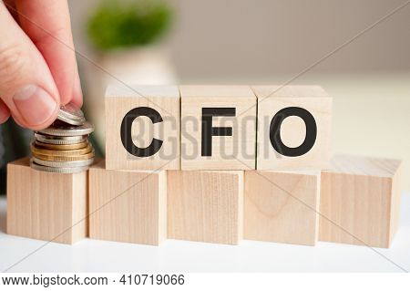 The Word Cfo Written On Wood Cubes. A Man's Hand Places The Coins On The Surface Of The Cube. Busine