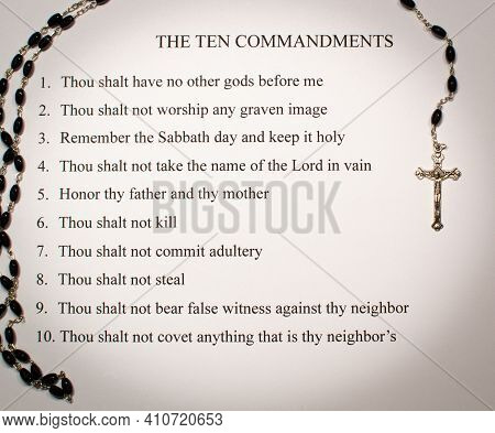 A Silver Rosary With Black Beads Surrounds The Ten Commandments From The Bible