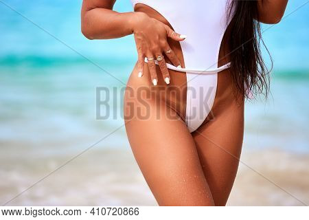 Close-up Tanned Parts Of Female Body On The Beach. Sexy Girl With A Beautiful Slender Figure Against