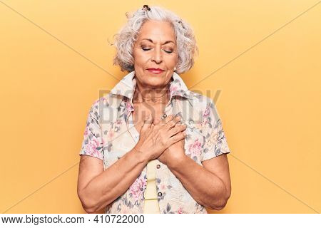 Senior grey-haired woman wearing casual clothes smiling with hands on chest with closed eyes and grateful gesture on face. health concept.