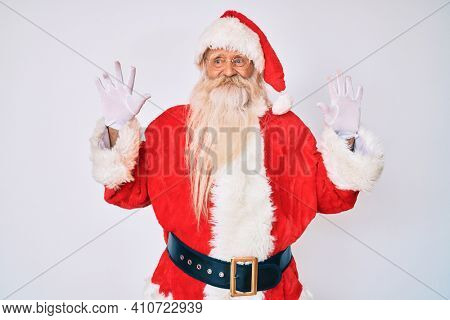 Old senior man with grey hair and long beard wearing santa claus costume with suspenders showing and pointing up with fingers number ten while smiling confident and happy.