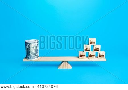 Pyramid Of Blocks With Industrial Factories And A Dollars Bundle Money On Scales. Subsidies Financia