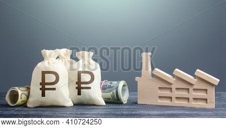 Russian Ruble Money Bags And Industrial Factory Figure. Subsidies Support For Businesses.concession