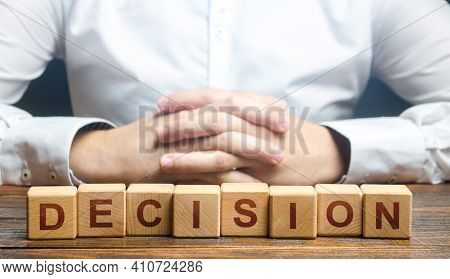 Man Folded His Hands On A Background Of Blocks With The Word Decision. Make The Right Decision, The