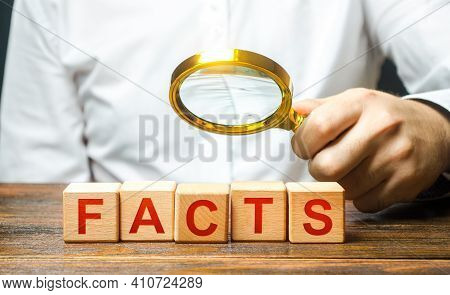 Man Examines The Blocks With Word Facts With A Magnifying Glass. Checking Facts And Data For Plausib