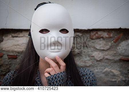 Young Unrecognized Woman With White Mask Covering The Face. Halloween, Carnival Face Masks At Festiv