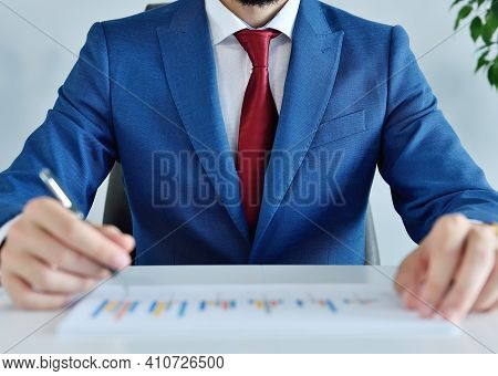 Accountant Sitting In Office And Analyzing Business Report. Business And Paperwork Concept. Close Up