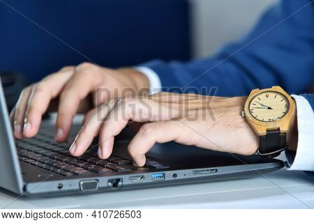Accountant Hands With Wooden Watch Typing On Laptop Keyboard. Occupation And Worker Concept. Close U