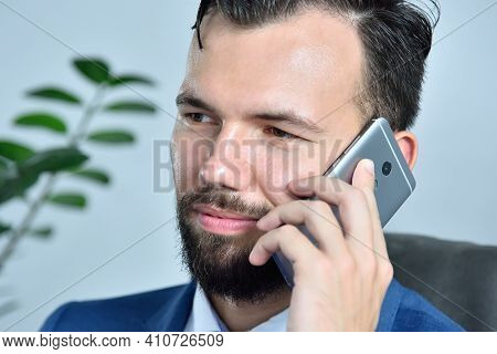 Young Bearded Businessman Working In Office And Talking On Mobile Phone. Occupation And Worker Conce
