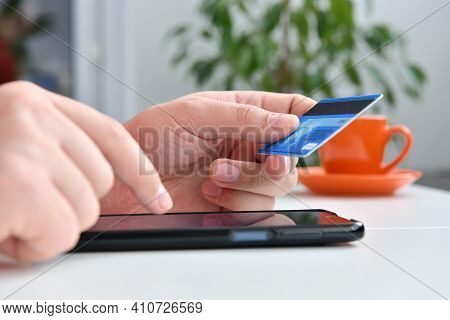 Man's Hands Holding Blue Credit Card And Using Smart Phone For Online Shopping. Online Shopping And
