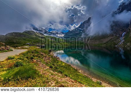 View of road running along green shores and small alpine lake under low clouds as mountains on background in Piedmont, Northern Italy.