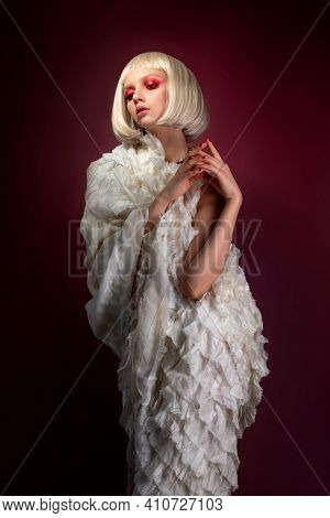 Fashion Portrait Of Young Blonde Woman Posing Over Dark Red Background