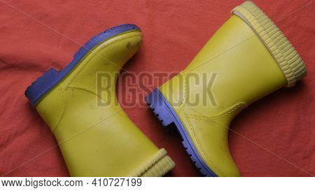 Dirty Pair Of Kids Yellow Rubber Boots Stop Orange Rag. Top View Pair Of Waterproof Rubber Boots Nee