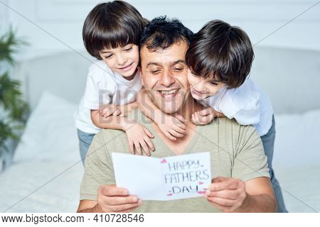 The Coolest Dad. Portrait Of Latin Father Looking Happy While His Two Little Boys Embracing Their Da