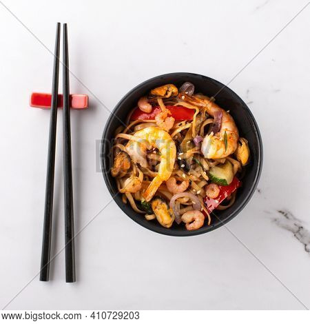 Stir fry noodles or wok noodles frying with prawns and mussels in black bowl and chopsticks side view on white marble background, top view.