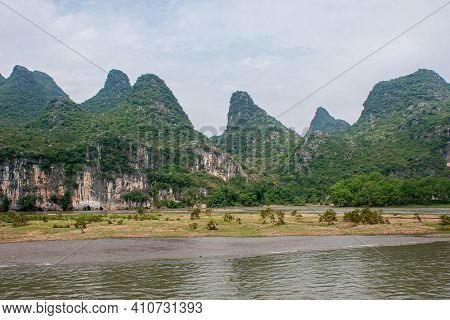 Guilin, China - May 10, 2010: Along Li River. Wide Landscape With Partly Submerged Flat Marshland Wi
