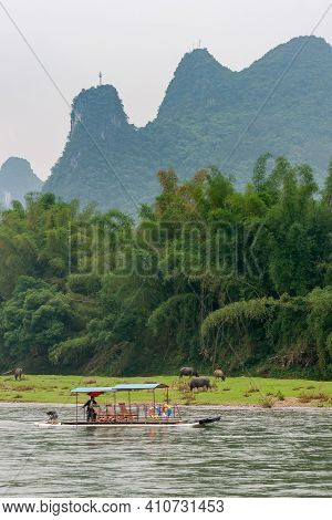 Guilin, China - May 10, 2010: Along Li River. Raft As Taxi On Green Water In Front Of Brown Buffalos