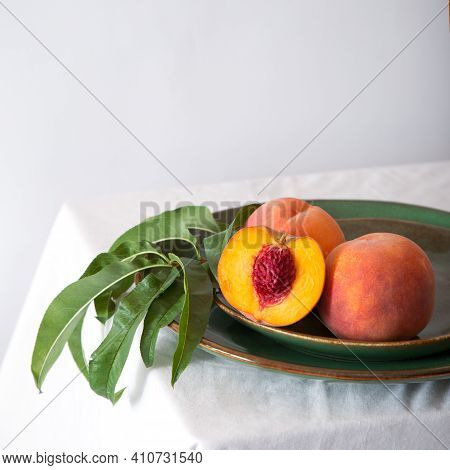 Peach In Halves With Bone In Minimalistic Style. Peaches With Leaves On Color Green Plate On Table W