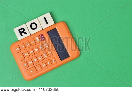 Calculator And Square Letters With Text Roi Stands For Return On Investment Over Green Background.