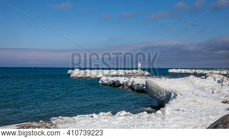 The Frozen Pier At The Entrance Of The Thornbury Yacht Club Marina In The Winter. Large Ice Sickles
