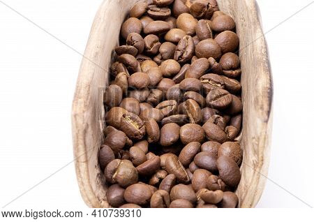 Coffee Beans In A Wooden Scoop Isolated On A White Background. Roasted Coffee Beans Isolated. A Wood