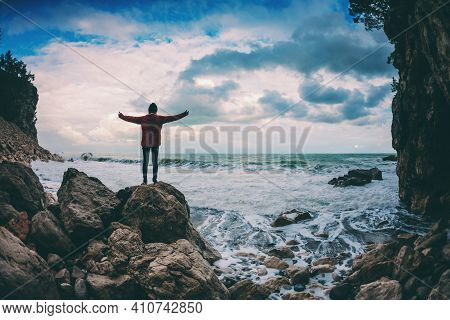 The Girl Stands On A Stone By The Sea. Woman Admires The Ocean. Silhouette Of A Person Against The S