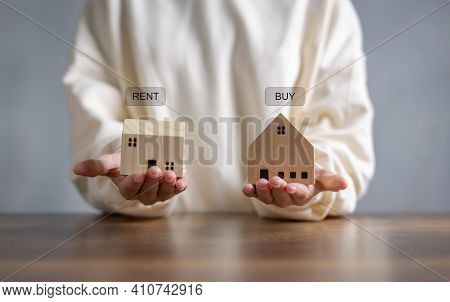 Hand Holding Wooden Home With Text Message Buy Or Rent, On Wooden Desk Office. Save Money And Buy Ho