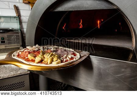 Restaurant Chef Takes Pizza From Oven In Traditional Restaurant. Preparing Traditional Italian Pizza