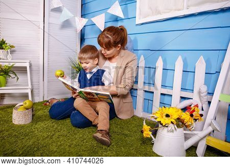 Mum Reading Fairy Tale Book To Child Son Sitting On Floor. Mother Reading A Book To Her Little Boy I