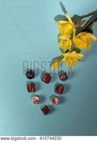 Yellow Daffodils And Chocolate Candies On Mint Background. Flat Lay,top View.